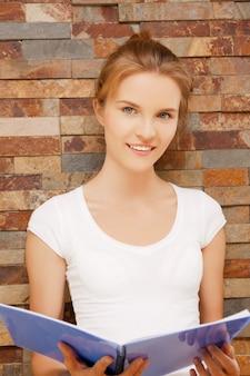Картина счастливой и улыбающейся девочки-подростка с большим блокнотом