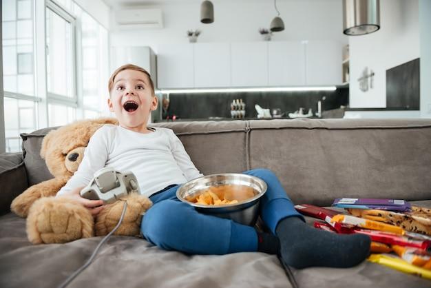 Изображение счастливого мальчика на диване с плюшевым мишкой дома, играющего в игры на консоли, пока ест фишки. удерживая джойстик.