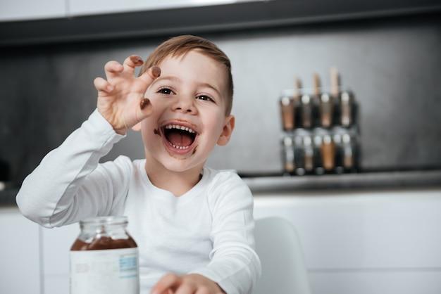 Изображение счастливого мальчика, стоящего на кухне во время еды. посмотри в сторону.
