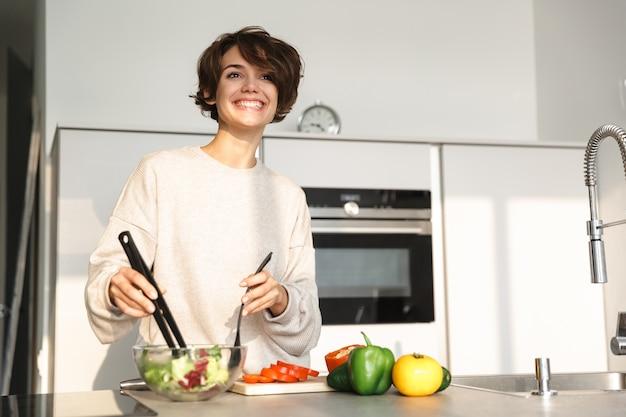 キッチンでテーブルのそばで料理をしながら目をそらしている幸せなブルネットの女性の写真