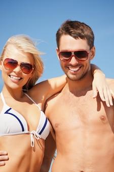 ビーチでサングラスをかけた幸せなカップルの写真(男性に焦点を当てる)。
