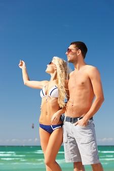 해변에서 선글라스를 끼고 행복한 커플 사진(남자에 초점)