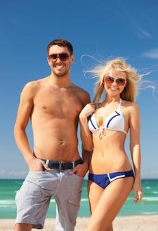 해변에서 선글라스를 쓴 행복한 커플의 사진.