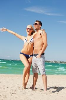 ビーチでサングラスをかけた幸せなカップルの写真。