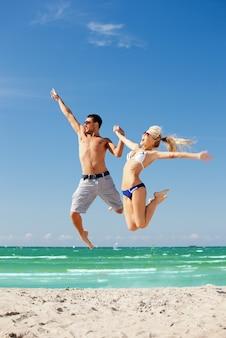 해변에서 점프하는 행복한 커플의 사진(남자에 초점)