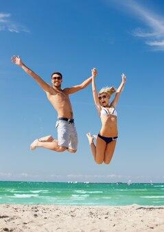 해변에서 점프 하는 행복 한 커플의 그림입니다.