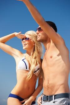 해변을 걷고 있는 행복한 커플의 사진(남자에 초점)