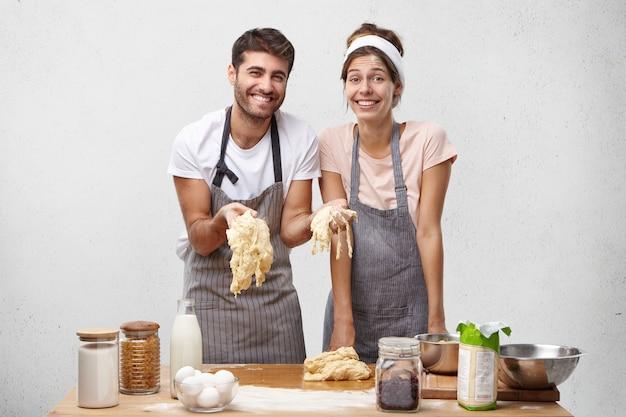 幸せな楽しい女性と男性の写真はパンを焼くための生地を準備します
