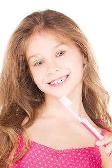 白の上の歯ブラシと幸せな女の子の写真