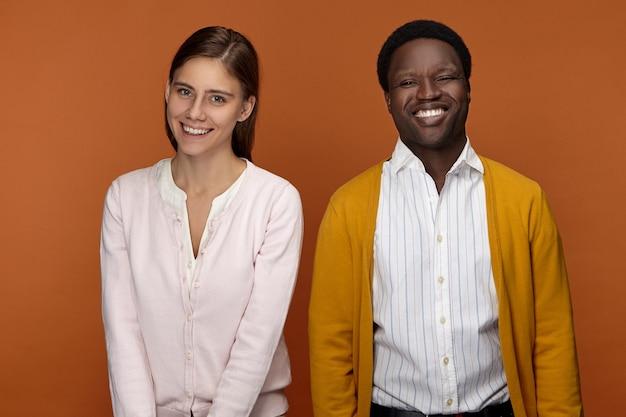幸せな愛情のある異人種間のカップルのポーズの写真。魅力的な若い白人女性と清楚な服を着た陽気なアフリカ人男性が広く笑顔で、喜びを表現し、良い前向きなニュースを受け取ります