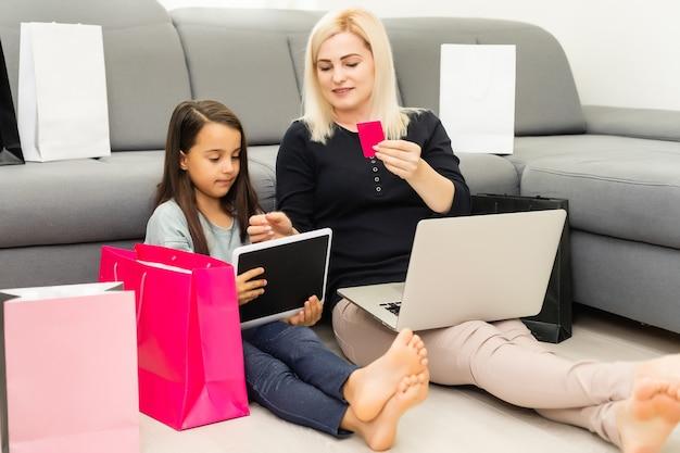 ラップトップコンピューター、オンラインショッピングで幸せな母と子の写真