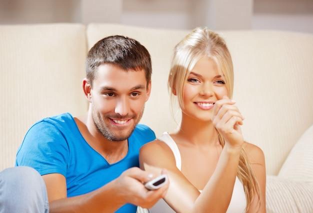 Картина счастливой романтической пары с пультом от телевизора (фокус на мужчине)