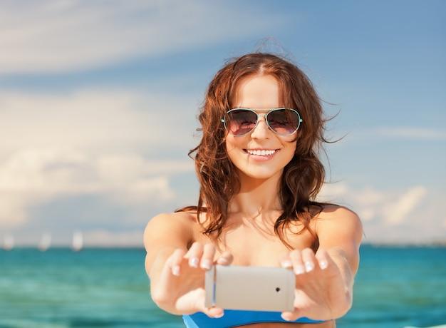전화 카메라를 사용 하 여 행복 하 게 웃는 여자의 사진입니다.