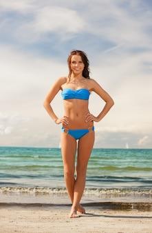 Картина счастливой улыбающейся женщины, идущей на пляже.