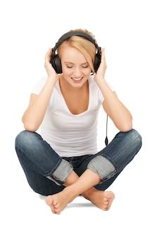 大きなヘッドフォンで幸せな10代の少女の写真