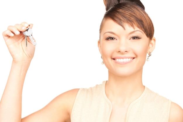 白の上のキーを持つ幸せな女性の写真