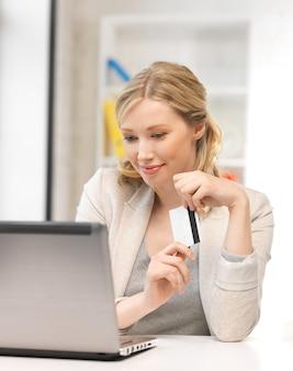 Изображение счастливой женщины с портативным компьютером и кредитной картой.