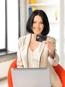 노트북 컴퓨터와 신용 카드를 가진 행복한 여성의 사진