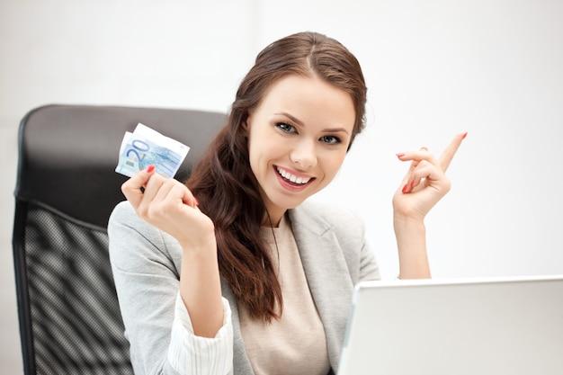Картина счастливой женщины с портативным компьютером и наличными деньгами евро