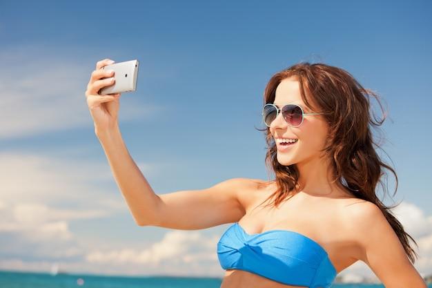 Изображение счастливой женщины с телефоном на пляже.