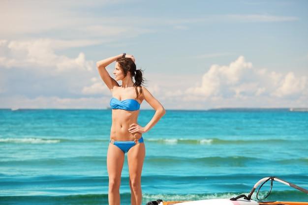 Картина счастливой женщины с серфингом на пляже.