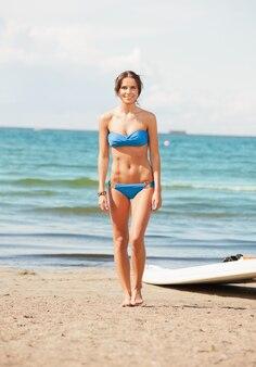 ビーチで風サーフィンと幸せな女性の写真。