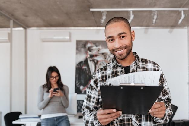屋内で幸せな若いビジネスパートナーの写真。クリップボードを持ってカメラを見てアフリカ人。人に焦点を当てます。