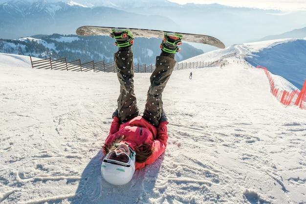 冬のリゾートの斜面で幸せな若い女性のスノーボーダーの写真