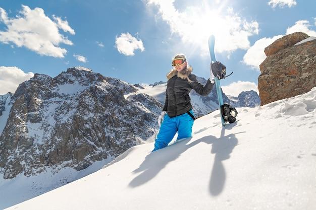 서리가 내린 겨울 날 슬로프에서 행복한 젊은 여성 스노우보더의 사진. 카메라를 봐.