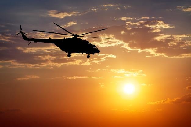Изображение вертолета на закате. силуэт вертолета на закатном небе.