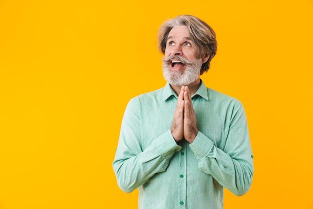 Изображение обнадеживающего эмоционального пожилого седого бородатого мужчины в синей рубашке, позирующего изолированно на желтой стене, показывающего жест, пожалуйста, помолитесь.