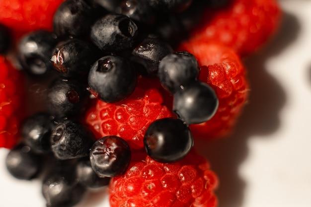 밝은 배경을 가진 흰색 세라믹 접시에 있는 신선하고 잘 익은 붉은 라즈베리와 블루베리 사진