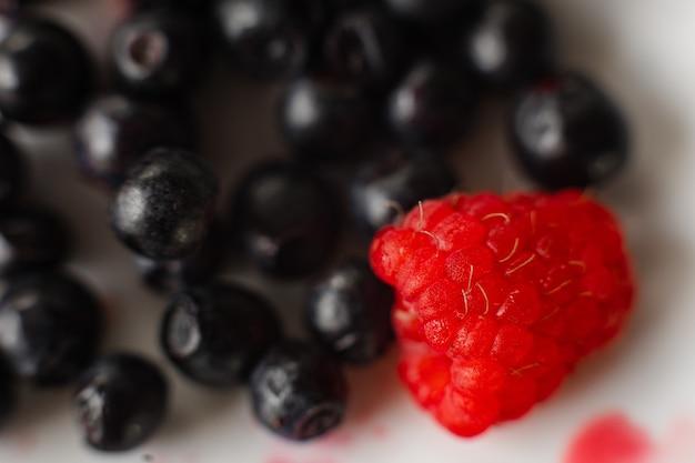 明るい背景と白いセラミックプレートのジューシーな新鮮な熟した赤いラズベリーとブルーベリーの画像