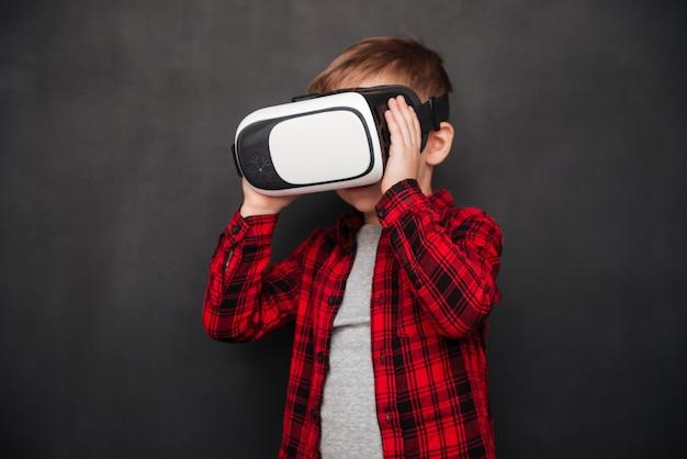 장치를 들고 칠판 위에 가상 현실 장치를 착용한 어린 아이의 사진