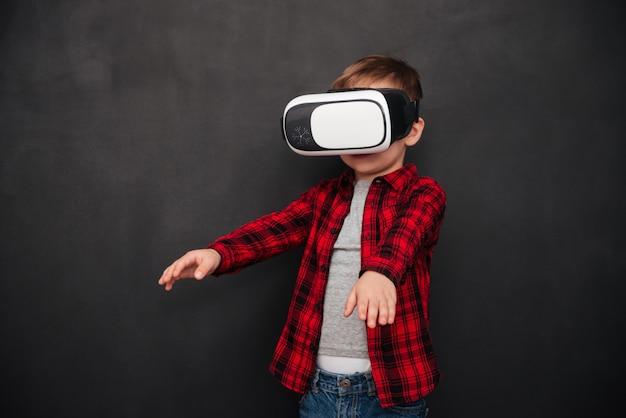 Изображение маленького ребенка в устройстве виртуальной реальности над доской