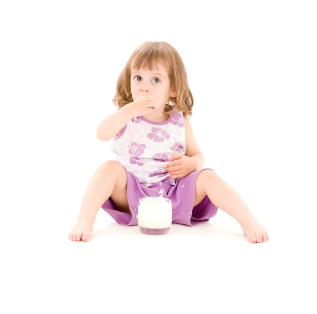 흰색 위에 요구르트를 먹는 어린 소녀의 사진