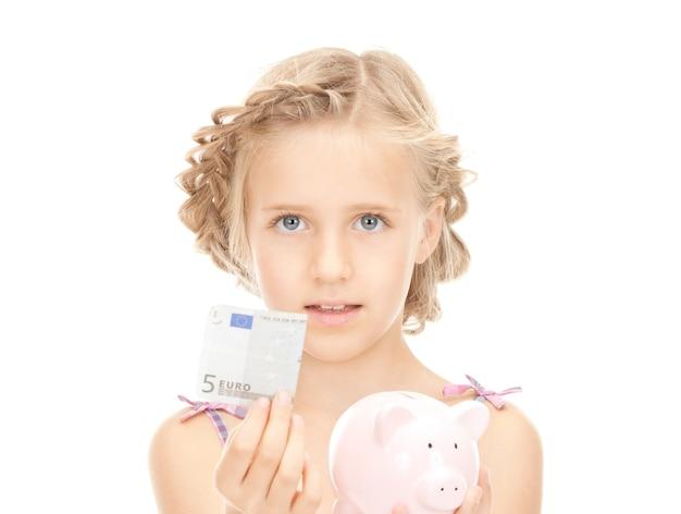 貯金箱とお金を持つ少女の写真