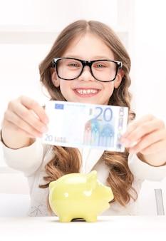 돼지 저금통과 돈을 가진 어린 소녀의 그림