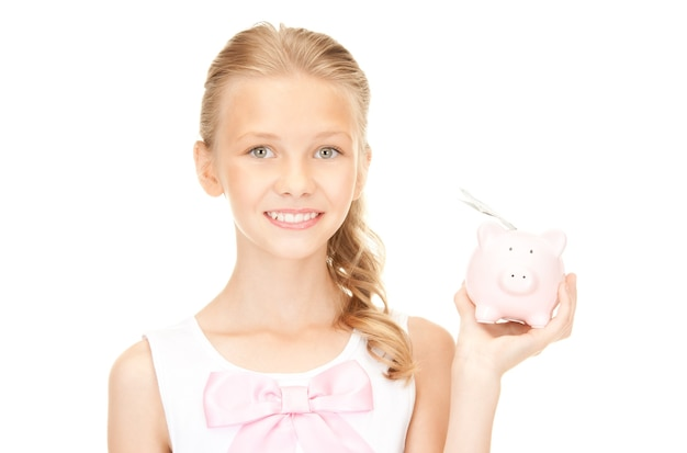 貯金箱とお金を持つ素敵な10代の少女の写真