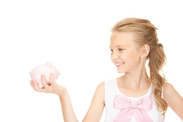 貯金箱を持つ素敵な10代の少女の写真
