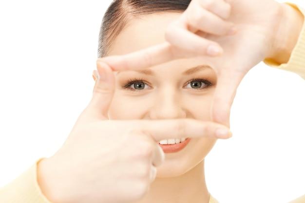 指でフレームを作成する素敵な女性の写真