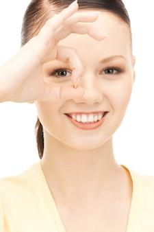 指から穴を通して見ている素敵な女性の写真
