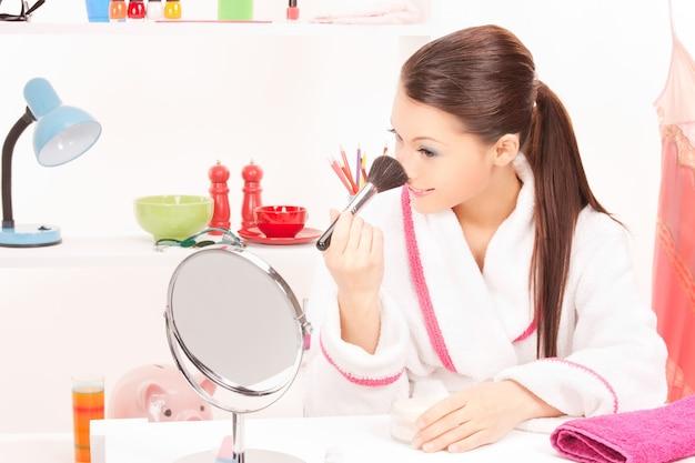브러시와 거울을 가진 사랑스러운 여자의 그림