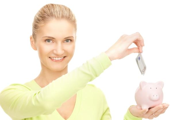 貯金箱とお金を持つ素敵な女性の写真