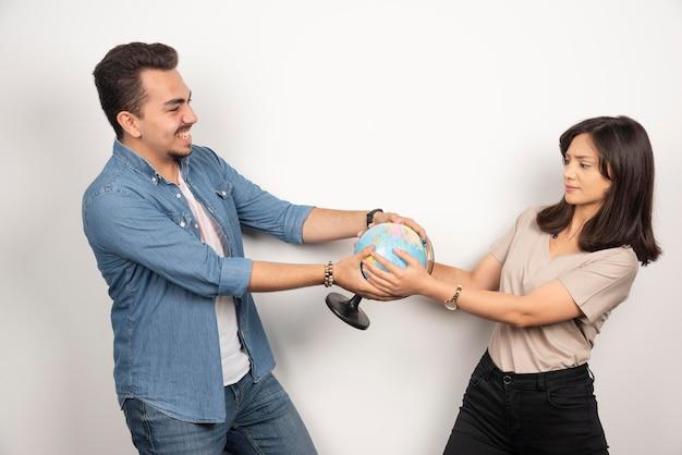 地球儀を持っている男性と女性の写真。