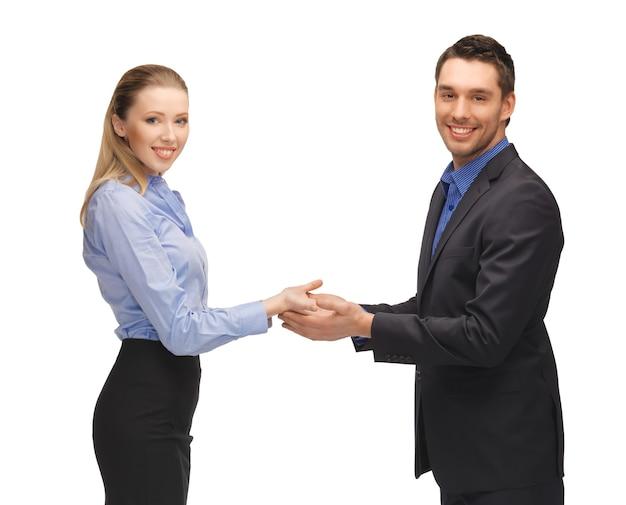 手のひらに何かを示している男性と女性の写真。