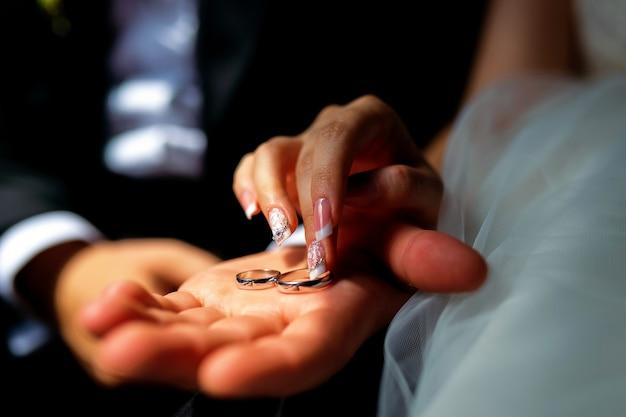 結婚指輪を持つ男女の写真。男の手にブライダルリング。手のクローズアップ。