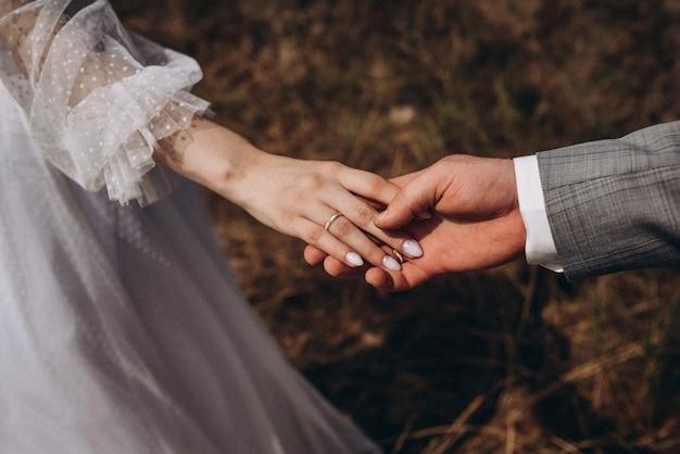 結婚指輪を持つ男女の写真。手をつないでいる若い夫婦、式典の結婚式の日。新婚カップルの手を結婚指輪で。