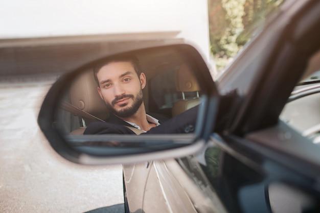 Изображение человека сидя в автомобиле и смотря зеркало крыла. он немного силсует. молодой человек доволен своей машиной. на улице ясно.
