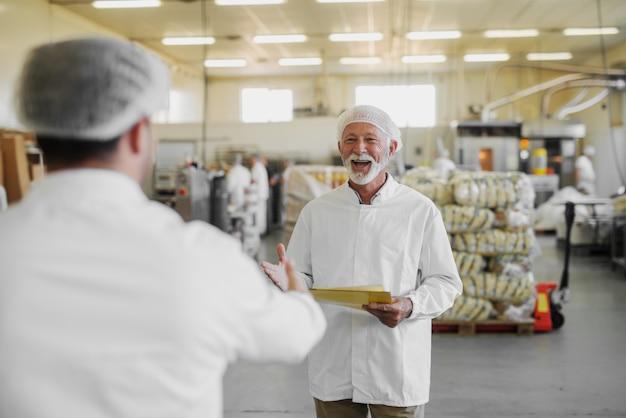 Изображение зрелого жизнерадостного пожилого человека в стерильной одежде, стоящего на пищевой фабрике и радующегося встрече со своим коллегой. работа в команде и концепция хорошей работы.